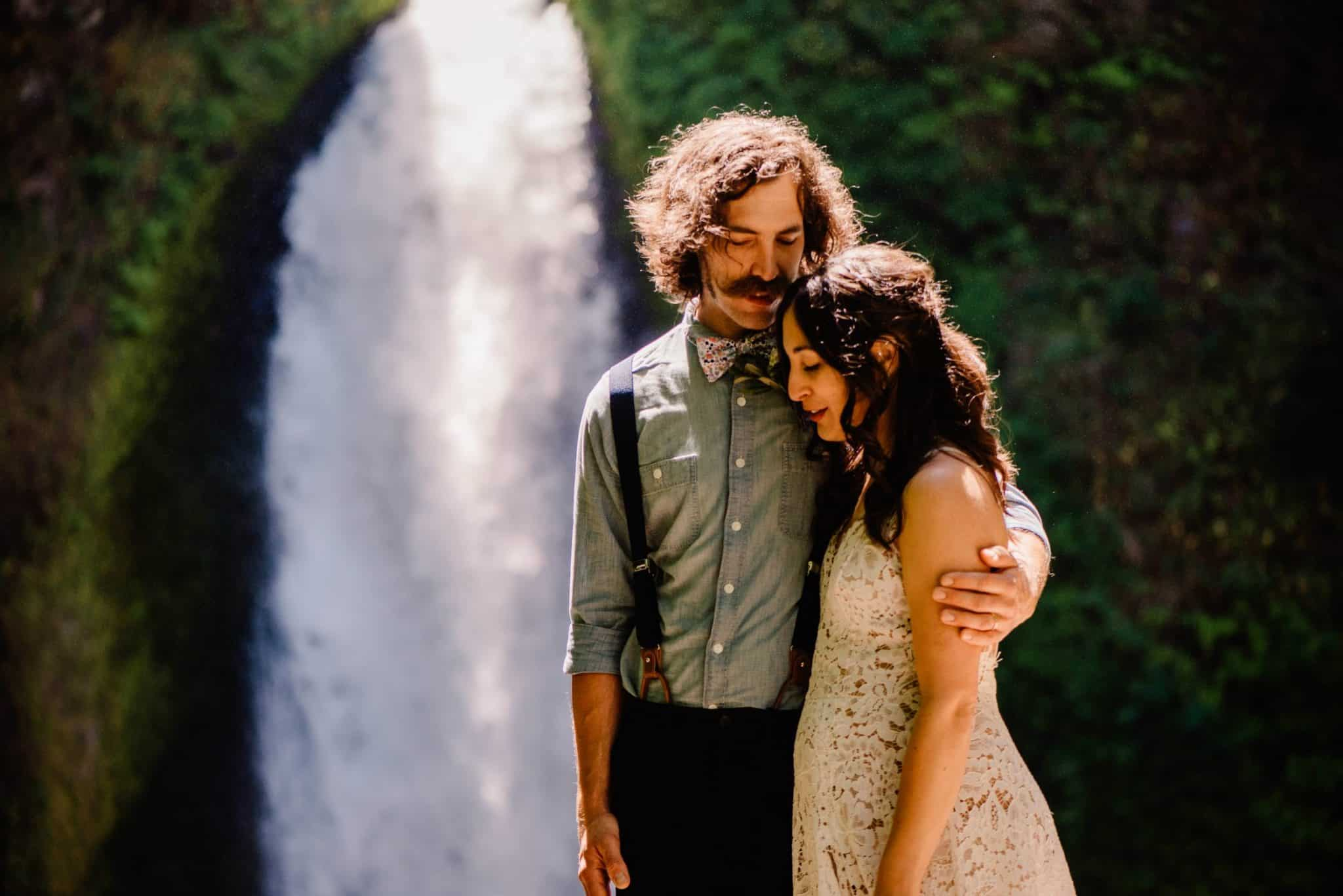 couple cutting with wahclella falls behind them