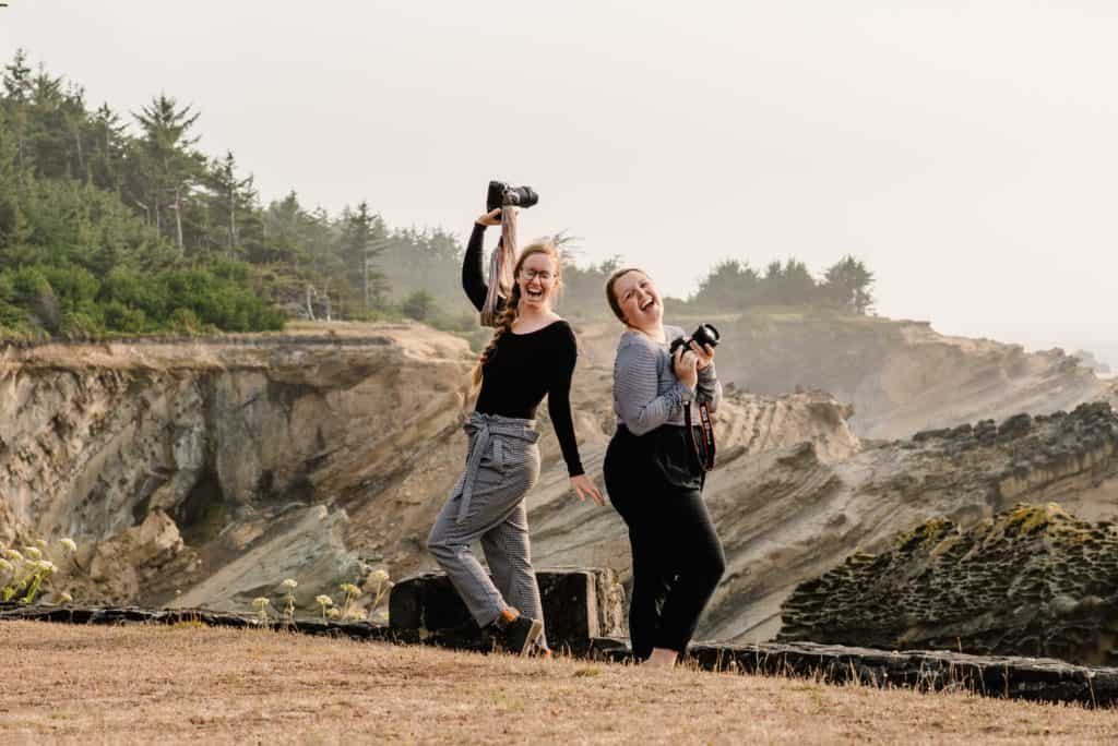 Emmy and Liv from Celebrate Again standing on the Oregon Coast with their cameras raised laughing