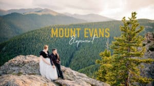 """""""Mount Evans elopement"""" couple sitting on a rock with a tree in the foreground and mount evans in the background on their wedding day"""